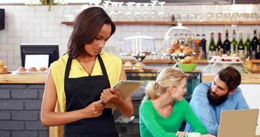 Smiling waitress holding a tablet video