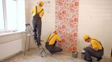 les constructeurs accrochent du papier peint dans l'appartement.