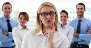 businesswoman looking at camera avec des collègues derrière elle