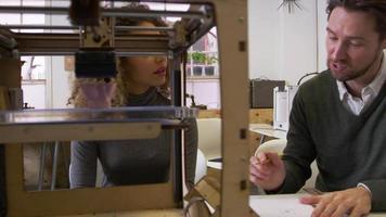 Zwei Designer, die in einem Designstudio arbeiten, sehen sich einen 3D-Drucker an, der auf R3D aufgenommen wurde video