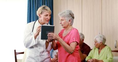 Doctora ayudando a la mujer mayor en tableta digital video