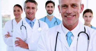 medico sorride alla telecamera con il team dietro di lui