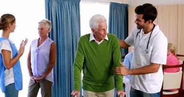 médecin aidant seniorman à marcher avec marcheur