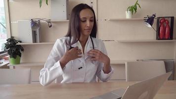 Médecin met sur la table phonendoscope regardant la caméra avec un sourire heureux video