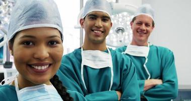 retrato de cirurgiões e enfermeira em pé com os braços cruzados na sala de operação video