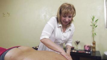 massaggiatrice specialista massaggia il lato sinistro della schiena all'uomo grasso adulto. colpo medio