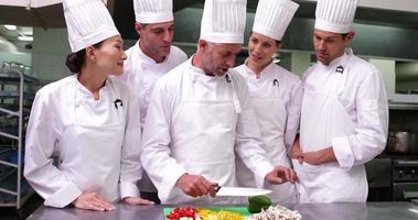 team di chef guardando il capo chef affettare le verdure