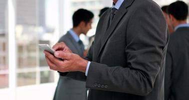 uomo d'affari utilizzando smartphone con i suoi colleghi dietro di lui