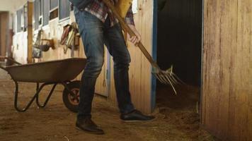 El hombre está limpiando un establo de heno con una horquilla.