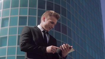Porträt des hellhäutigen Geschäftsmannes, der draußen an einem sonnigen Sommertag steht und an Tablette arbeitet video