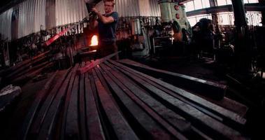Forgeron manipulant le fer rougeoyant en atelier video