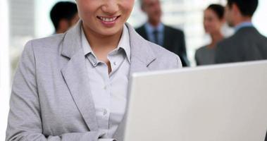 mulher de negócios usando seu laptop com seus colegas atrás