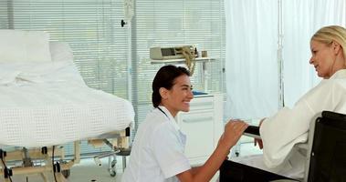 medico che parla con il paziente in sedia a rotelle
