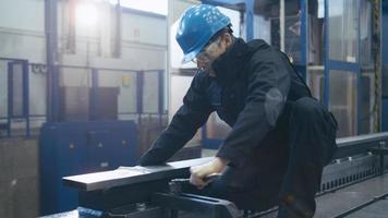 Industriearbeiter zieht in einer Fabrik Schrauben mit einem Schraubenschlüssel fest.