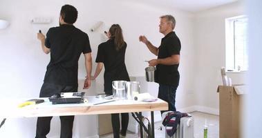 Decorador instruyendo a colegas sala de pintura con rodillos