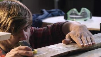 carpentiere che controlla pezzo di legno levigato
