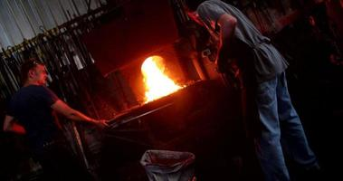 Blacksmith working in metal industry forging iron at furnace video