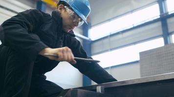 trabalhador industrial está apertando parafusos com uma chave inglesa em uma fábrica. video