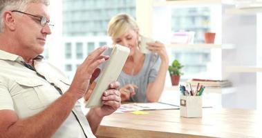 sorridenti colleghi casuali utilizzando la tavoletta digitale in ufficio