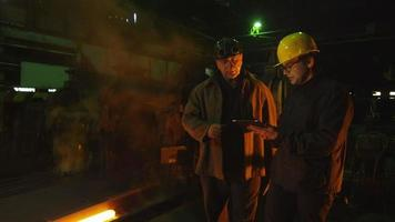 ingeniero y trabajador tienen conversación en fundición. ingeniero con tableta. entorno industrial accidentado.