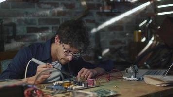 estudiante estudia electrónica y suelda una placa de circuito en un garaje. video