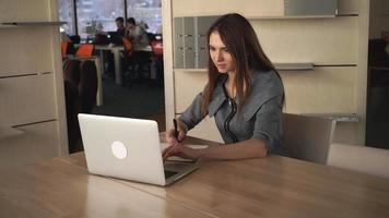 femme d & # 39; affaires, écrire des notes dans le cahier et vérifier les données dans l & # 39; ordinateur
