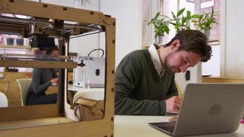 designer che disegna in uno studio di stampa 3d e controlla il computer, girato su r3d