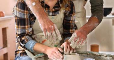 alfarero masculino ayudando alfarero femenino video