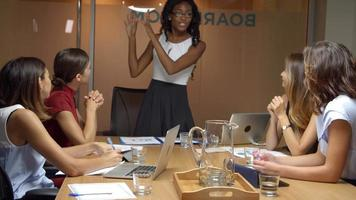 schwarze Chefin steht beim Geschäftstreffen vor dem Team video