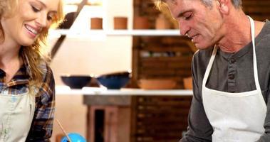 männliche und weibliche Töpfer malen auf Schüssel in der Töpferwerkstatt video