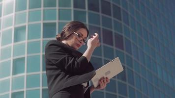 Attractive dark-haired business woman wearing spectacles using her tablet to work outdoors video