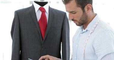 Handsome tailor using tablet beside suit on mannequin video