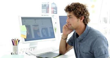 bel giovane designer creativo che telefona con il suo telefono video