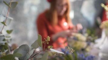 fleurs sur fond flou fleuriste fille faisant une composition de fleurs