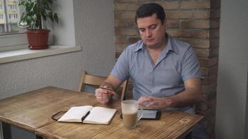 hombre de mediana edad paga facturas a través de internet en manos de la tarjeta de crédito video