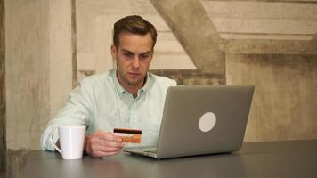 Online banking. The man sits by the table and hold credit card