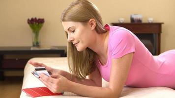 Hermosa joven atractiva acostada en el sofá y comprar en línea con tarjeta de crédito en tableta negra video