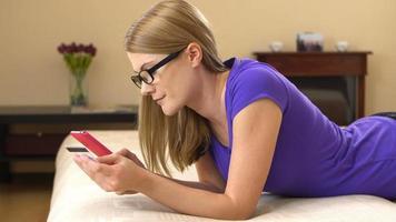 bella giovane donna attraente sdraiata sul divano con uno smartphone e lo shopping online