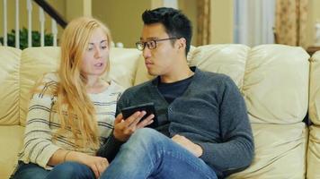 joven pareja multiétnica pasa tiempo en casa. disfruta de la tableta video