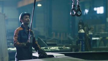 Schwerindustrie-Arbeiter in einer Fabrik bedienen einen Kran mit Fernbedienung.