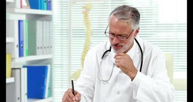 ritratto di un medico serio che lavora sulla sua scrivania