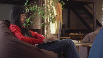 asiatische Frau, die am Laptop im Dachboden mit Holztreppen arbeitet