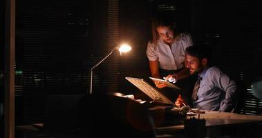 Kollegen, die nachts ein Tablet benutzen