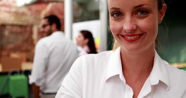casual businesswoman smiling at camera avec équipe derrière elle