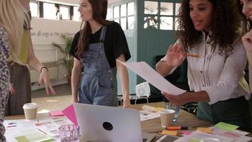 Diseñadoras reunidas alrededor de la mesa en la oficina rodada en r3d video