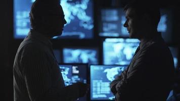 Zwei männliche Angestellte unterhalten sich in einem dunklen Überwachungsraum mit Bildschirmen.