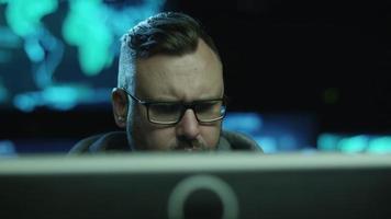 imagens de retrato de um empregado concentrado do sexo masculino trabalhando em um computador em uma sala escura de escritório com telas de exibição com mapas e dados. video