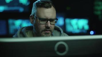 imágenes de retrato de empleado masculino concentrado trabajando en una computadora en una habitación oscura de oficina con pantallas de visualización con mapas y datos. video