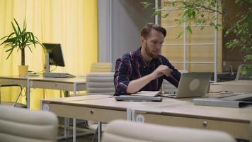 empresario barbudo trabajando en una computadora y tomando café