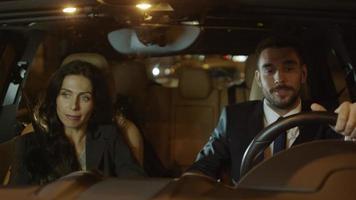 atractivo empresario y mujer hablando en un coche por la noche